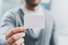 De mens die van de close-upfoto toevallig overhemd dragen en leeg wit adreskaartje tonen Vage achtergrond Klaar voor privé Royalty-vrije Stock Fotografie