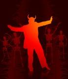 De mens die van de duivel met skeletten op de achtergrond danst Royalty-vrije Stock Foto