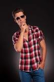 De mens die van de manier zonnebril en het denken draagt Royalty-vrije Stock Afbeeldingen