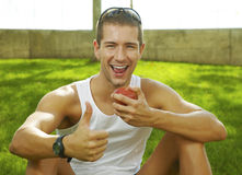 De mens die van de sport het teken o.k. toont en een appel eet Royalty-vrije Stock Foto's