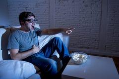 De mens die van de televisieverslaafde op bank op TV in het grappige nerd geek glazen gek lachen letten Stock Foto's