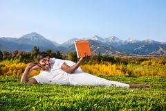 De mens die van de yoga het boek leest Stock Fotografie