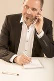 De mens die van het arbeidersbureau op de mobiele telefoon spreken Royalty-vrije Stock Afbeelding