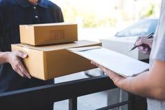 De mens die van de leveringspost pakketdoos geven aan de begunstigde, Jonge mens die ontvangstbewijs van leveringspakket thuis on stock afbeelding