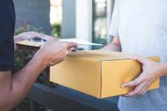 De mens die van de leveringspost pakketdoos geven aan ontvanger en handtekeningsvorm, Jonge eigenaar die ontvangstbewijs van leve stock foto