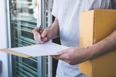 De mens die van de leveringspost pakketdoos geven aan ontvanger en handtekeningsvorm, Jonge eigenaar die ontvangstbewijs van leve stock fotografie