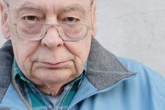 De mens die van oudsten glazen draagt Stock Foto