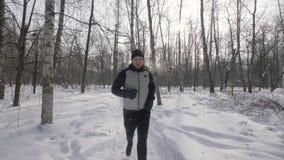 De mens die van de portretatleet in de winter bos dichte omhooggaand lopen De winterjogging in stadspark stock video