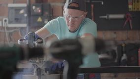 De mens die van de portretvaardigheid in beschermingsglazen een houten raad met een kleine cirkelzaag op de lijst in de workshop  stock footage