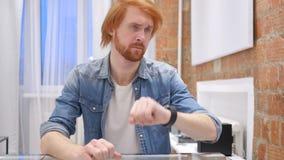 De Mens die van de roodharigebaard bij het Werk, het Letten op Tijd aangaande Horloge wachten stock footage