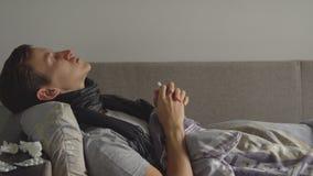 De mens die ziek in bed naast zijn medicijnen in zijn huis liggen en bestrooit een neusnevel in zijn neus stock video