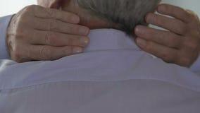 De mens die zijn hals opwarmen, voelend pijn en ongemak, vermoeide van het bureauwerk stock videobeelden