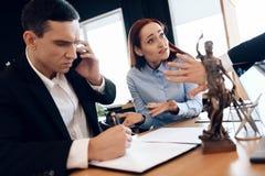 De mens die zijn vrouw scheidt raadpleegt over telefoon met advocaat De verontruste vrouw zit naast de mens die op telefoon sprek stock fotografie