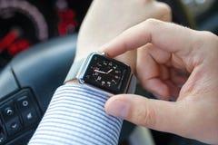 De mens dient de auto met het Horloge en de Klok van Apple in Stock Foto's
