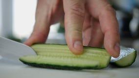 De mens dient Keuken in Snijdend een Komkommer in Plakken voor een Verse Salade royalty-vrije stock foto