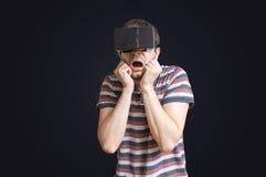 De mens draagt 3D virtuele werkelijkheidshoofdtelefoon en is doen schrikken van iets Stock Foto