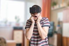 De mens draagt 3D virtuele werkelijkheidshoofdtelefoon en is doen schrikken van iets Stock Foto's