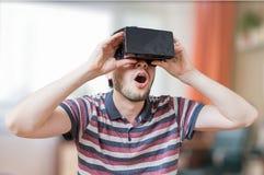 De mens draagt 3D virtuele werkelijkheidshoofdtelefoon en is gefascineerd stock foto's