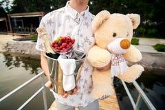 De mens draagt een emmer van champagne en teddybeer stock afbeelding