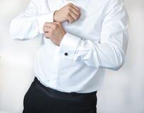 De mens draagt manchetknopen op een overhemdskoker Een bruidegom die op manchetknopen zetten aangezien hij in formele slijtage ge Royalty-vrije Stock Fotografie