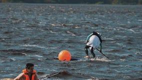 De mens draagt pandakostuum op een surfplank probeert om rond baken te berijden gebruikend peddel stock videobeelden