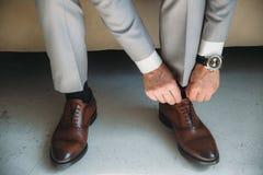 De mens draagt schoenen Bind het kant op de schoenen Mensen` s stijl tref voor het werk voorbereidingen, aan de vergadering royalty-vrije stock fotografie