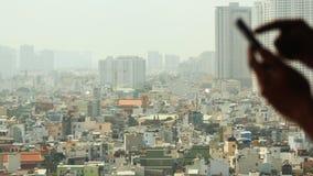 De mens draait de telefoon tegen de achtergrond van de stad van venster 2 stock videobeelden