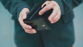 De mens draait een lege portefeuille in zijn hand stock video