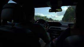 De mens drijft auto en de vrouw vindt door navigator verpletter, zittend binnen een bewegende auto in dag in de zomer stock videobeelden