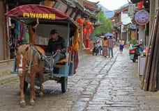 De mens drijft door paarden getrokken voertuig in Lijiang royalty-vrije stock afbeelding