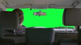 De mens drijft een auto tegen een groene achtergrond stock footage