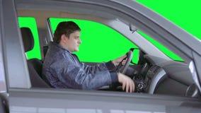 De mens drijft een auto tegen een groene achtergrond stock videobeelden
