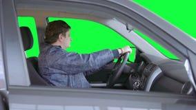 De mens drijft een auto tegen een groene achtergrond stock video