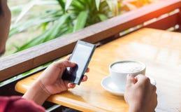 De mens drinkt koffie en gebruiks slimme telefoon in koffiewinkel royalty-vrije stock afbeelding