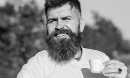 De mens drinkt koffie Koffie gastronomisch concept De gebaarde mens met espressomok, drinkt koffie stock afbeelding
