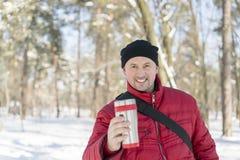 De mens drinkt thee uit kop De winter bos Jonge mens in een rood warm jasje met gebreide hoed en sjaal die zich op sneeuwachtergr royalty-vrije stock fotografie
