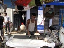 De mens drukt kleren gebruikend een traditioneel houtskool verwarmd ijzer Royalty-vrije Stock Foto
