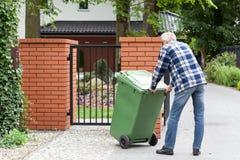 De mens duwt dumpster op wielen Royalty-vrije Stock Fotografie