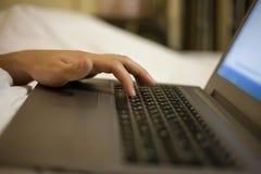 De mens duwt op sleutels die op laptop in bed liggen Stock Afbeeldingen