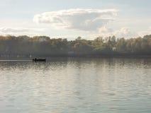 De mens in een boot drijft langs de rivier Royalty-vrije Stock Fotografie