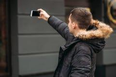 De mens in een grijs jasje bevindt zich buiten en gebruikt een telefoon stock fotografie