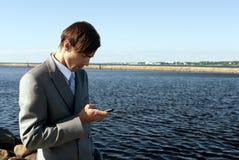De mens in een grijs kostuum draait de telefoon Royalty-vrije Stock Foto