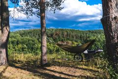 De mens in een hangmat op pijnboom bosberg, openluchtreiziger ontspant, enduro van wegmotorfiets stock foto's
