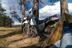 De mens in een hangmat op pijnboom bosberg, openluchtreiziger ontspant, enduro van wegmotorfiets stock afbeelding