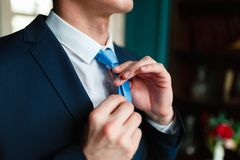 De mens in een klassiek kostuum maakt zijn blauwe band recht Knappe elegante jonge maniermens in klassieke het kostuumkostuum en  stock afbeeldingen