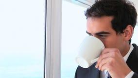 De mens in een kostuum kijkt uit de venster toen dranken stock footage