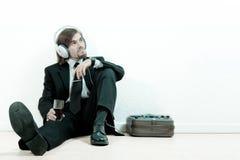 De mens in een kostuum luistert aan de muziek stock afbeeldingen