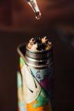 De mens in een vapewinkel vult een speciale vloeistof in e-sigaret Stock Foto's