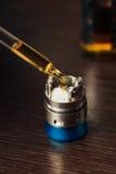 De mens in een vapewinkel vult een speciale vloeistof in e-sigaret Royalty-vrije Stock Foto's