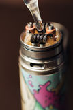 De mens in een vapewinkel vult een speciale vloeistof in e-sigaret Stock Afbeeldingen